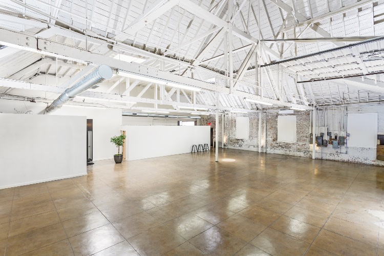 Modern Warehouse Space: A 6000 sqft warehouse space, with 2 large roll-up doors on the ground level, 20' - 30' ceilings, vaulted ceilings, 6 exposed trusses, whitewashed brick walls, wide expansive spaces, bright with 6 skylights, clean, modern and comfortable. Two large restrooms, separate production, hair and makeup areas, kitchenette with dual sinks, storage space and large refrigerator and can furnish with tables chairs, makeup stations, and other essentials.  Space used by many for its warehouse aesthetic, or as a stage for its expansiveness and use flexibility.